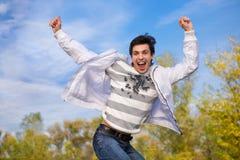 O homem novo feliz salta no ar foto de stock royalty free