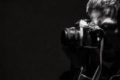 O homem novo fotografa uma foto preto e branco da câmera velha retro Fotografia de Stock Royalty Free