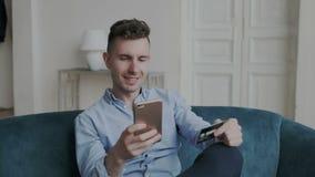 O homem novo glamoroso e encantador que compra em linha usa um telefone e um cartão de crédito no sofá em casa Imagina sua compra video estoque