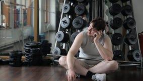 O homem novo grosso no gym sorri, falando no smartphone filme