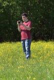 O homem novo guarda a câmera entre flores amarelas no prado Foto de Stock Royalty Free