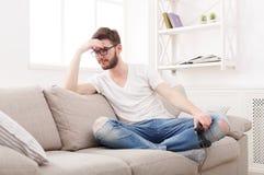 O homem novo infeliz que joga jogos de vídeo e perde foto de stock royalty free