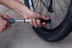 O homem novo infla a roda de bicicleta foto de stock