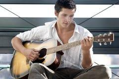 O homem novo joga a guitarra Foto de Stock
