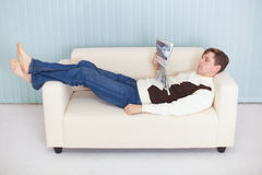 O homem novo lê o compartimento que encontra-se no sofá imagem de stock royalty free