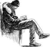 O homem novo lê um livro Fotografia de Stock Royalty Free