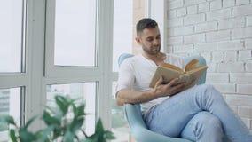 O homem novo leu o livro que senta-se no balcão no apartamento moderno vídeos de arquivo