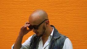 O homem novo lindo na roupa das calças de brim com veste óculos de sol pretos filme