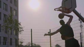 O homem novo marcou uma bola na aro de basquetebol exterior vídeos de arquivo