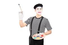 O homem novo mimica o artista que guarda um pincel Fotografia de Stock Royalty Free