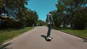 O homem novo monta o longboard no parque video estoque