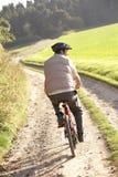 O homem novo monta sua bicicleta no parque Fotos de Stock
