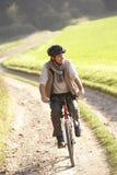 O homem novo monta sua bicicleta no parque Fotografia de Stock