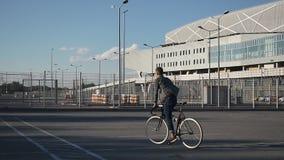 O homem novo monta uma bicicleta ao longo da rua vídeos de arquivo