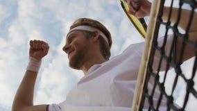 O homem novo mostra o gesto do vencedor, fica a rede próxima do tênis, bom jogo, vista inferior filme