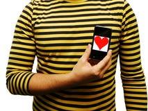 O homem novo mostra o coração no telefone móvel. Imagem de Stock Royalty Free