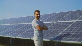 O homem novo mostra o polegar acima no fundo dos painéis solares video estoque