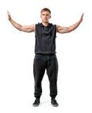 O homem novo Muscled está de empurrão paredes invisíveis com suas mãos no fundo branco imagens de stock royalty free