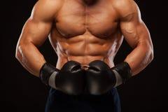 O homem novo muscular com o torso perfeito com seis Abs do bloco, em luvas de encaixotamento está mostrando os movimentos e as gr Foto de Stock