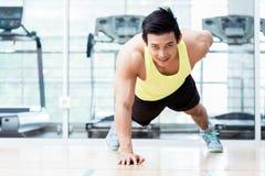 O homem novo muscular que faz um armou flexões de braço no gym Imagens de Stock