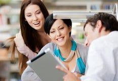 O homem novo na biblioteca mostra a almofada a duas mulheres Fotos de Stock