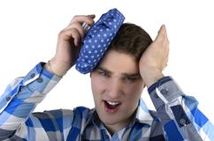 O homem novo na camisa azul tem a dor de cabeça má foto de stock royalty free