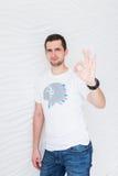 O homem novo na camisa branca de t mostra o sinal aprovado da mão imagens de stock royalty free