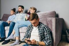 O homem novo na camisa verificada está enviando sms quando seus amigos olharem a tevê imagem de stock