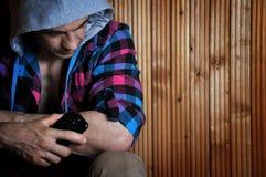 O homem novo na capa, assento do moderno, posses telefona e olha para baixo no fundo marrom de madeira Imagens de Stock