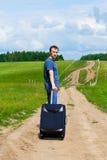 O homem novo na estrada no campo com uma mala de viagem Foto de Stock