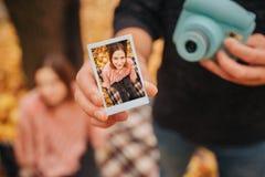 O homem novo na roupa preta mostra a imagem em uma mão e a câmera em outra Há jovem mulher na foto Senta-se sobre fotos de stock royalty free