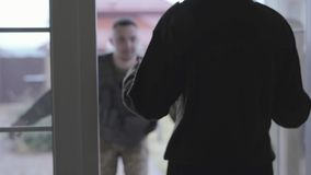 O homem novo nas forças armadas fecha-se com o saco grande que vai à casa, nas portas abertas que estão a mulher que guarda o pap vídeos de arquivo