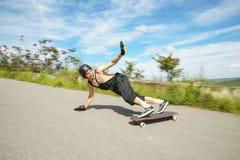 O homem novo no capacete está indo deslizar, para deslizar com faíscas em um longboard no asfalto imagens de stock royalty free