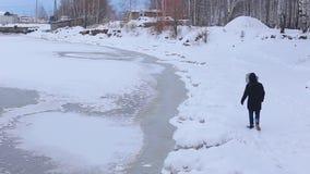 O homem novo no revestimento preto com capa da pele está no banco coberto de neve do rio congelado e verifica o gelo video estoque