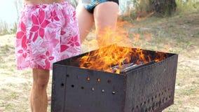 O homem novo no short ajusta um fogo em seu metal Blazier em um banco de rio no Slo-Mo filme