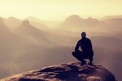 O homem novo no sportswear preto está sentando-se na borda do penhasco e está olhando-se ao fole enevoado do vale Foto de Stock