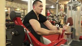 O homem novo no t-shirt preto está treinando no gym filme