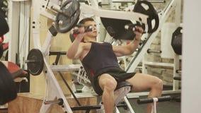 O homem novo no t-shirt preto está treinando no gym video estoque