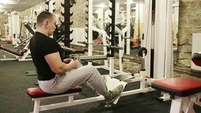 O homem novo no t-shirt preto está treinando no gym vídeos de arquivo