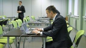 O homem novo no terno de negócio com relógio de pulso caro está trabalhando com o portátil que senta-se na cadeira verde atrás da vídeos de arquivo