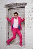 O homem novo no terno e em sapatas cor-de-rosa está com na parede Fotos de Stock Royalty Free