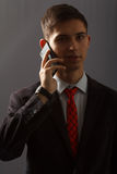 O homem novo no terno está falando no telefone da venda Imagens de Stock Royalty Free