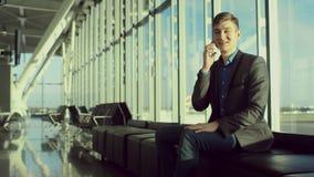 O homem novo no terno está falando sobre um telefone celular no aeroporto filme
