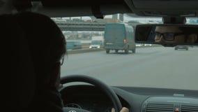 O homem novo nos vidros que conduzem um carro em uma cidade grande video estoque