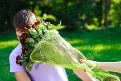 O homem novo obtem a batida no ramalhete da face de rosas vermelhas Imagens de Stock Royalty Free