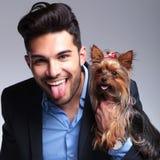 O homem novo ocasional guarda o cachorrinho e as calças Imagem de Stock Royalty Free