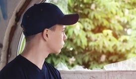O homem novo olha em uma janela quebrada velha Fotografia de Stock