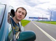 O homem novo olha fora do indicador de carro Fotografia de Stock Royalty Free
