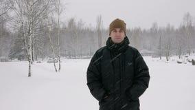 O homem novo olha na câmera e no sorriso na queda de neve grande da floresta do inverno Um homem em um revestimento escuro e em u filme