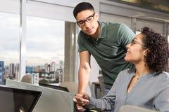 O homem novo olha o empregado quando mostrar um projeto fotos de stock royalty free